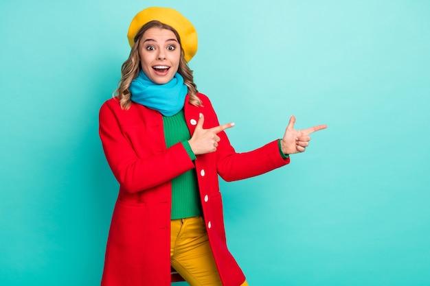 Portrait d'une promotrice de fille positive étonnée présente des publicités incroyables promotion point index copyspace impressionné crier wow omg porter un pantalon pantalon isolé fond de couleur sarcelle
