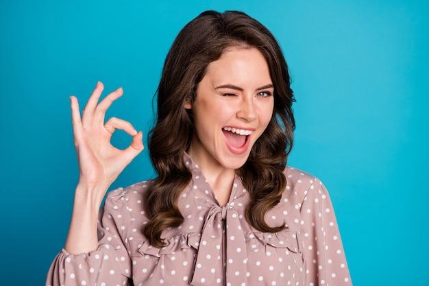 Portrait d'une promotrice positive et joyeuse, profitez d'excellentes publicités promotionnelles, affichez un signe d'accord, portez des vêtements de bonne apparence isolés sur fond de couleur bleue