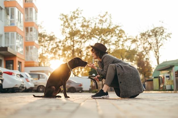 Portrait de propriétaire de fille et beau chien en laisse assis sur rue