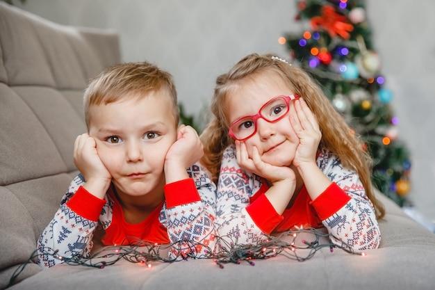 Portrait de quatre ans - frère et soeur jumeaux en pyjama à la maison sur le canapé avec arbre de noël