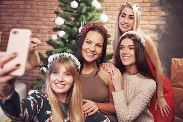 Portrait de quatre fille souriante avec corolle sur la tête faire photo selfie. sentiment de nouvel an. joyeux noël