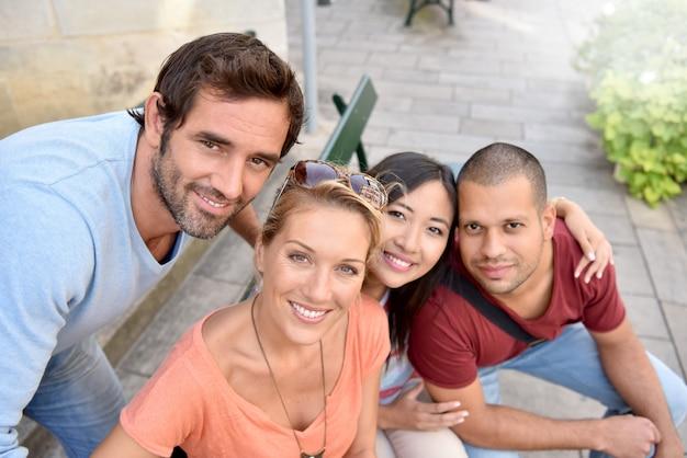 Portrait de quatre jeunes adultes assis sur un banc en ville