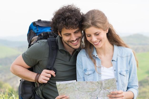Portrait de randonneurs heureux analyser la carte en sentier