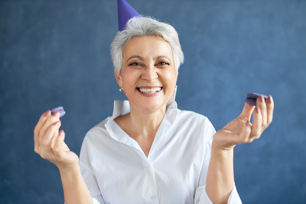 Portrait de ravie charmante femme d'âge moyen souriant largement tenant des macarons, profitant d'un délicieux dessert sucré à la fête d'anniversaire.