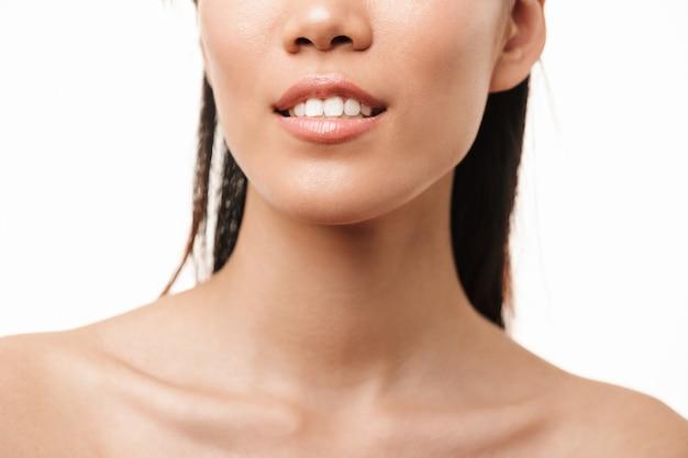 Portrait recadré d'une belle jeune jolie femme asiatique avec une peau saine posant isolée sur un mur blanc