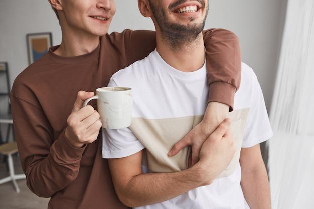 Portrait recadré d'un couple gay insouciant embrassant tout en se tenant près de la fenêtre et profitant du matin ensemble à la maison, espace de copie