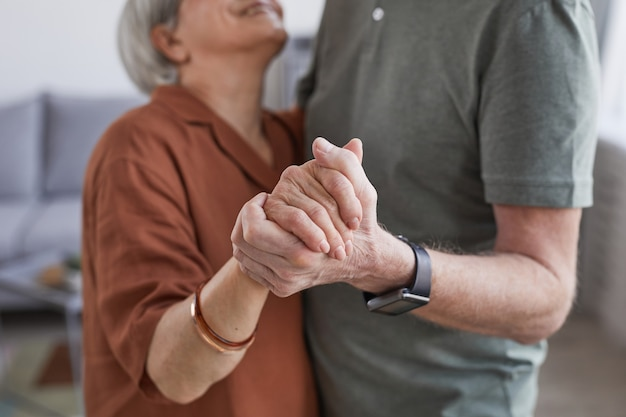 Portrait recadré d'un couple de personnes âgées aimant danser à la maison ensemble et se tenant la main
