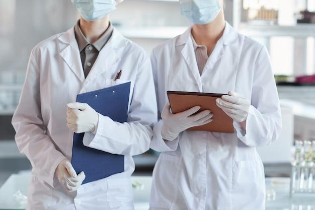 Portrait recadré de deux femmes scientifiques portant un masque facial et tenant des planchettes en position debout dans un laboratoire médical