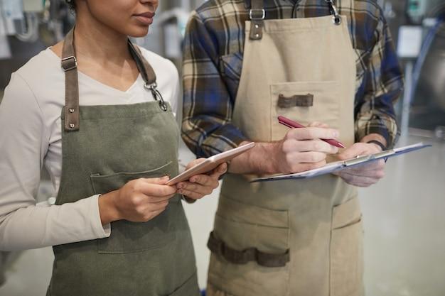 Portrait recadré de deux jeunes travailleurs utilisant une tablette numérique tout en supervisant la production dans une brasserie artisanale moderne, espace de copie