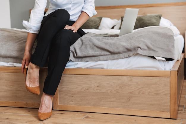 Portrait recadré d'une femme d'affaires adulte de race blanche en costume formel enlevant ses chaussures alors qu'il était assis sur le lit et utilisant un ordinateur portable dans un appartement