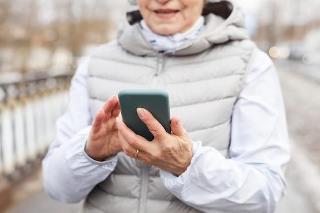 Portrait recadré d'une femme senior moderne tenant un smartphone à l'extérieur en hiver, espace pour copie