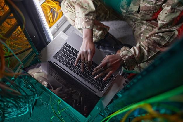 Portrait recadré en grand angle d'une jeune femme afro-américaine portant un uniforme militaire tout en utilisant un ordinateur dans la salle des serveurs