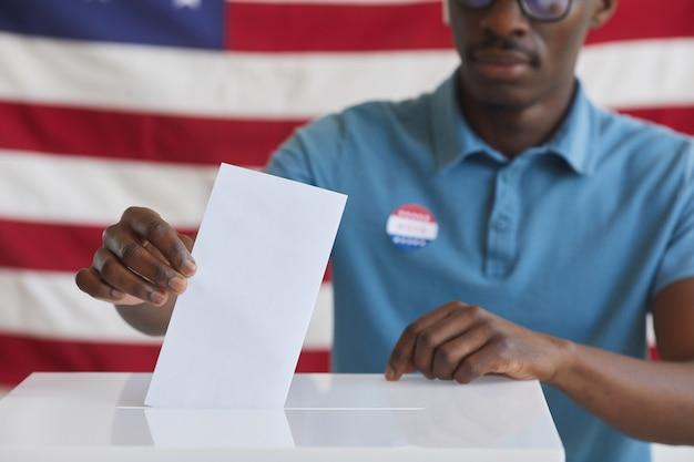 Portrait recadré de l'homme afro-américain mettant bulletin de vote dans l'urne en se tenant debout contre le drapeau américain le jour de l'élection, copiez l'espace