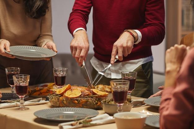 Portrait recadré d'un homme méconnaissable coupant une délicieuse dinde rôtie tout en appréciant le dîner de thanksgiving avec des amis et la famille,