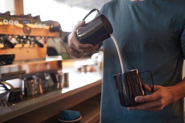 Portrait recadré d'un jeune barista versant de la crème dans un café au lait tout en préparant du café frais dans un café ou un café, espace pour copie