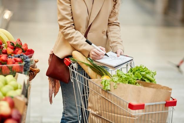 Portrait recadré de jeune femme méconnaissable tenant une liste de courses tout en achetant des produits d'épicerie au supermarché ou au marché de producteurs