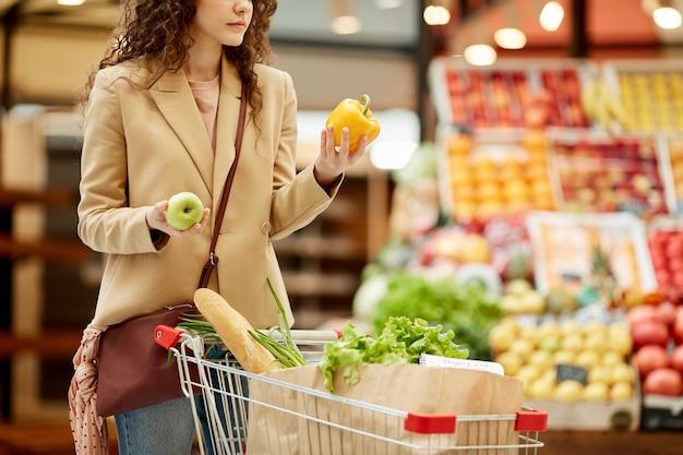 Portrait recadré de jeune femme moderne tenant le poivron tout en choisissant des fruits et légumes frais au marché de producteurs