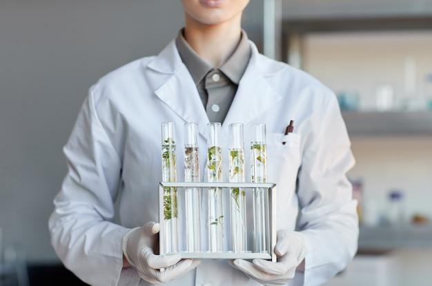 Portrait recadré de jeune femme scientifique tenant des tubes à essai avec des échantillons de plantes tout en travaillant sur la recherche en laboratoire de biotechnologie, espace copie