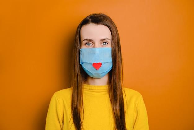 Portrait recadré d'une jolie jeune femme européenne portant un masque de santé avec un cœur rouge dessus pour montrer son appréciation et remercier tous les employés essentiels pendant la pandémie de covid-19.