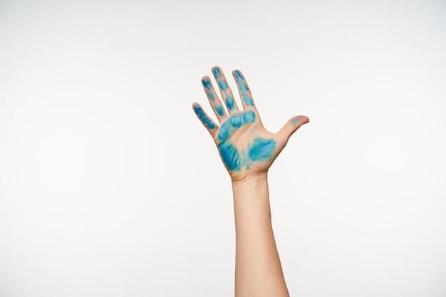Portrait recadré de la main de jolie femme à la peau claire montrant la paume surélevée avec de la peinture bleue dessus, debout sur blanc. concept de mains et de signes humains