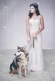 Portrait de la reine des glaces et chien de traîneau parmi la neige qui tombe