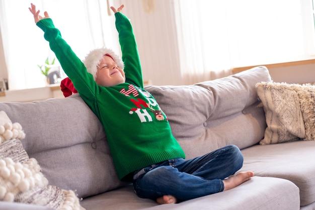 Portrait de rêve garçon aux yeux fermés en bonnet de noel et costume de noël assis à la maison les mains