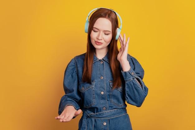 Portrait de rêveuse jolie dame mignonne porter des écouteurs sans fil écouter de la musique s'imaginer dj sur fond jaune
