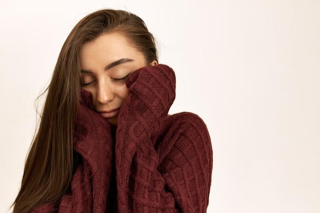Portrait de rêveuse pensive jeune femme mignonne aux cheveux bruns lâches posant isolée dans un pull chaud à manches longues, gardant les yeux fermés, rêvant de vacances ensoleillées au bord de la mer, souriant joyeusement