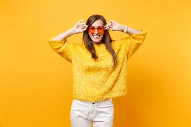 Portrait de rire heureux jeune femme en pull de fourrure, pantalon blanc tenant des lunettes orange coeur isolé sur fond jaune vif. les gens émotions sincères, concept de style de vie. espace publicitaire.