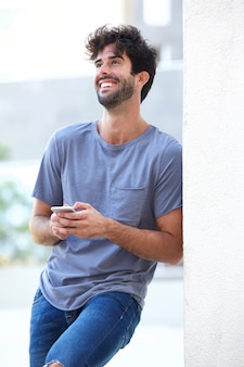Portrait, de, rire, tenue, téléphone, penchant, mur, dehors