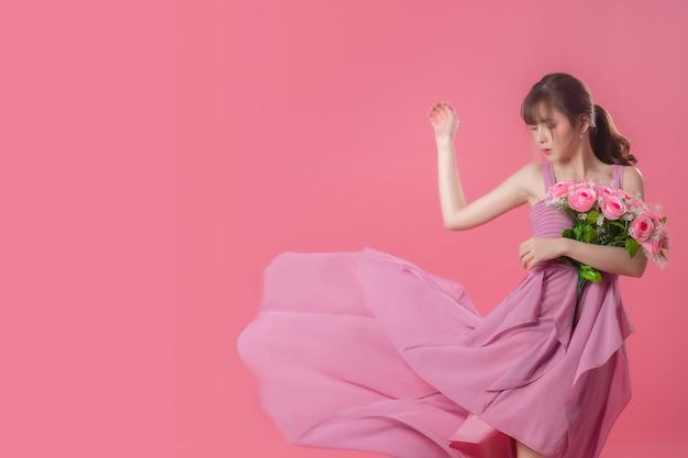 Portrait de robe rose fluide avec des pétales volants sur rose