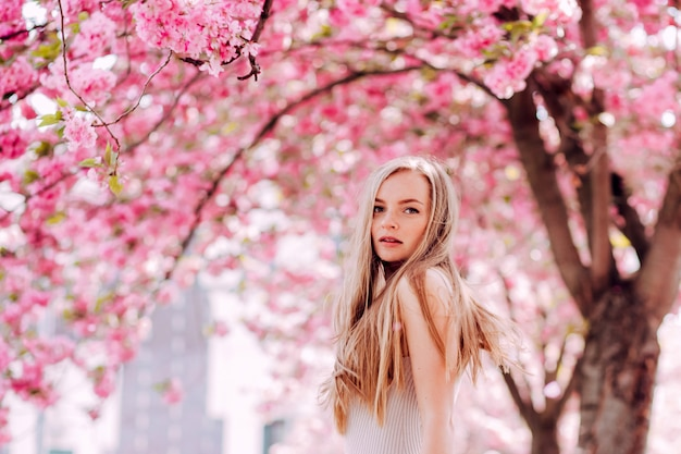 Portrait romantique d'une charmante blonde sur le mur d'un jardin fleuri. arbre à fleurs roses. beauté femme blonde aux cheveux longs à l'extérieur. fleurs de cerisier. bouchent le portrait. sakura