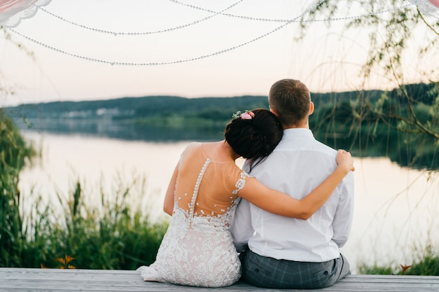 Portrait romantique de derrière de couple de mariage assis sur un pierce en bois au coucher du soleil et profiter du coucher de soleil sur le lac.