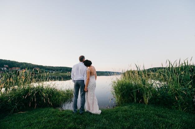 Portrait romantique de derrière le couple de mariage en regardant grand lac au coucher du soleil.