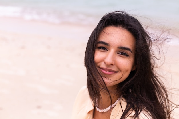 Portrait romantique de femme sur la plage au jour venteux, lumière chaude du coucher du soleil.