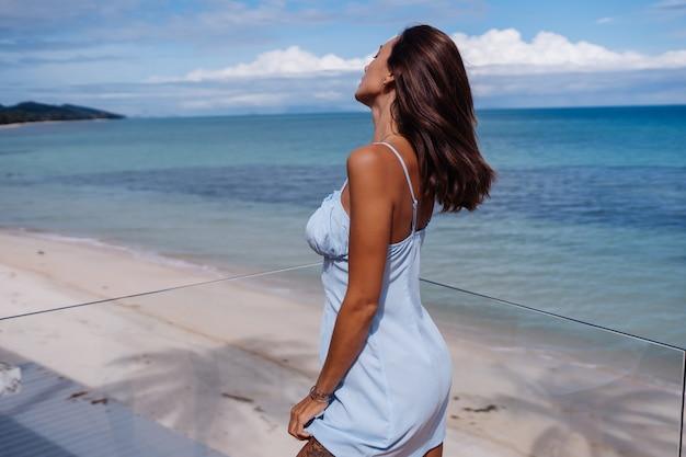 Portrait romantique de femme en robe de lumière bleue seule sur la plage tropicale, journée ensoleillée, peau foncée bronzée