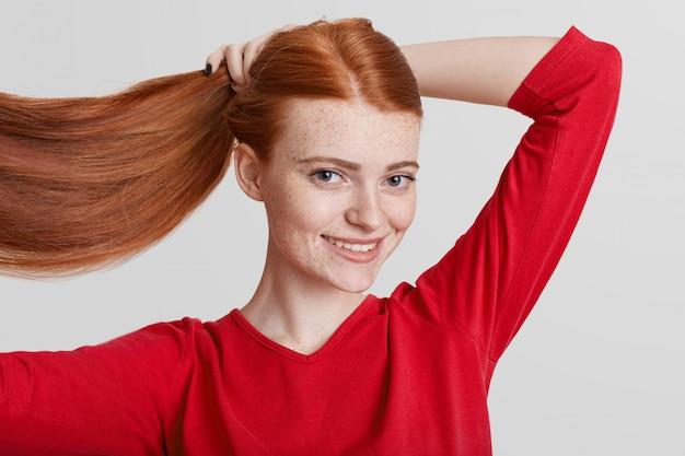 Portrait de rousse heureuse jolie jeune femme montre ses longs cheveux luxueux, fait queue de cheval, va marcher avec des amis, regarde directement dans l'appareil photo, pose contre le blanc
