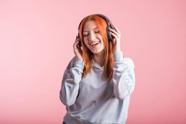 Portrait d'une rousse joyeuse qui écoute de la musique sur des écouteurs en studio sur fond rose