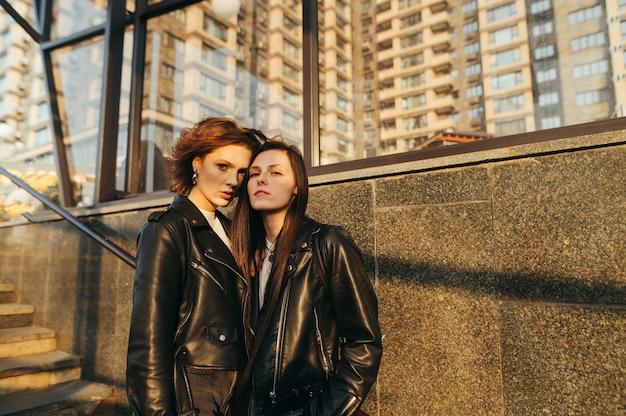 Portrait de rue de deux jolies filles en vestes de cuir debout