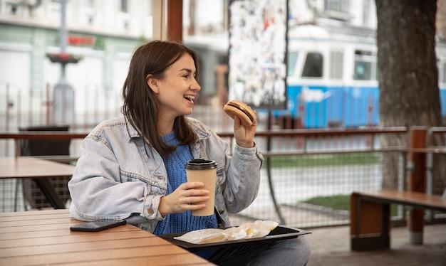 Portrait de rue d'une jeune femme gaie appréciant un hamburger et un café dehors
