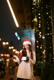 Portrait de rue de nuit de la belle jeune femme agissant ravi. lumières de guirlande festives.