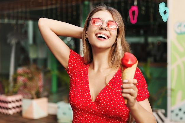Portrait de rue en plein air d'une femme heureuse, manger de la crème glacée