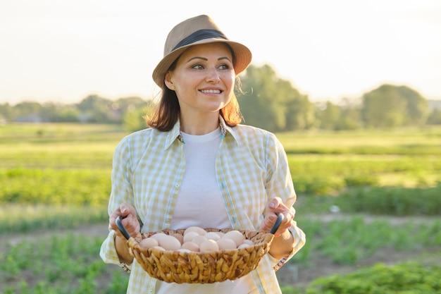 Portrait rustique de femme mature avec panier d'oeufs au pré