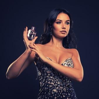 Portrait sans retouche belle femme avec bouteille de parfum rose sur un espace sombre.