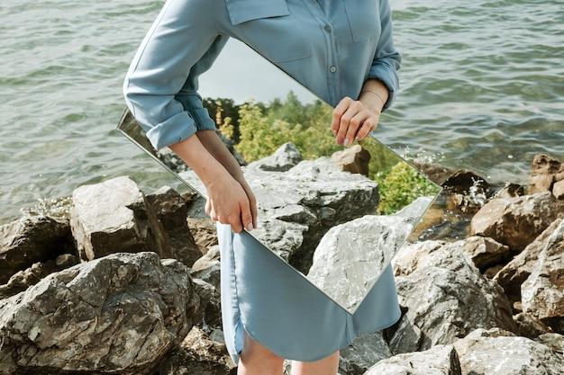 Portrait sans visage de femme debout sur un rivage en robe bleue