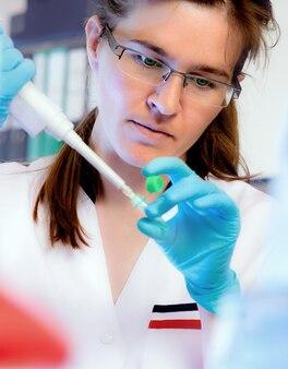 Portrait d'un scientifique avec un distributeur automatique de liquide dans un laboratoire moderne, dof peu profonde