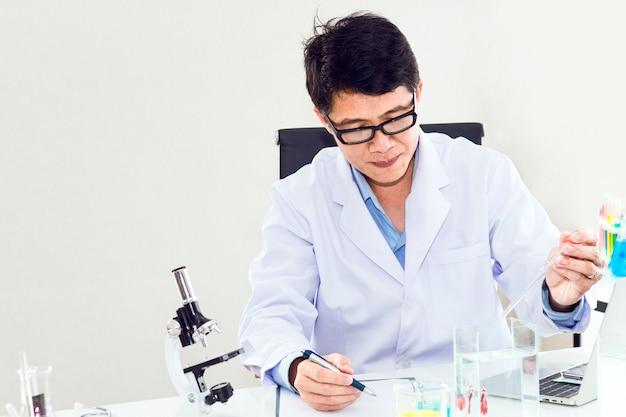 Portrait d'un scientifique mature souriant dans une blouse blanche à la loupe.