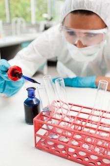 Portrait d'un scientifique protégé laissant tomber un liquide bleu dans un test