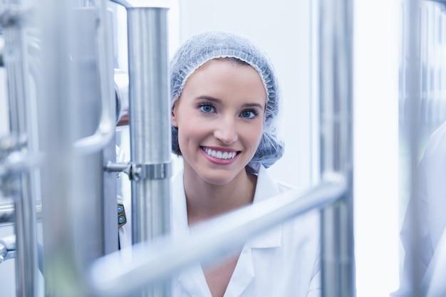 Portrait d'un scientifique souriant derrière un tuyau métallique