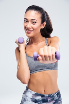 Portrait d'une séance d'entraînement de femme fitness souriant avec des haltères isolé sur un mur blanc